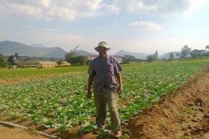Bishop Trevor Manhanga midden op de grond die rijkelijk vrucht draagt